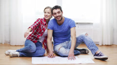 smiling couple discussin blueprint at home - stock footage