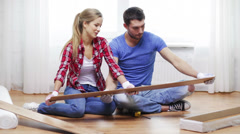 Couple taking out wood flooring from package Stock Footage