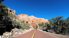 POV vehicle road drive sandstone cliffs blue sky extreme terrain Zion Utah - stock footage