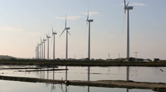Salt ponds and turbines at wind farm Stock Footage