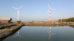 Rotating turbines and salt ponds at wind farm Stock Footage