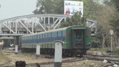 TRAIN - LOCOMOTIVE: Green train departs with white pylons in foreground - stock footage