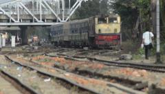 TRAIN LOCOMOTIVE: Track level view of yellow and red train approaching - stock footage