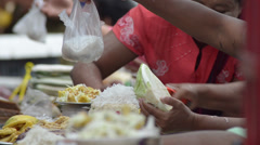ASIA MARKET: Close up sellers' hands, handing bag of food Stock Footage