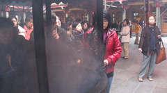 Woman praying with incense in Taoist temple. Taipei Stock Footage