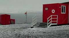Snowstorm at the Gabriel Castilla Station flag Spanish, arngentina, Red Cross Stock Footage