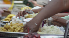 ASIA MARKET: Close up shot of seller's hand preparing food on plate Stock Footage