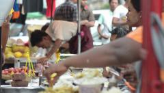 ASIA MARKET: Side view of multiple food sellers at streetside stand Stock Footage