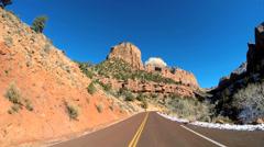 POV road drive sandstone rock blue sky snow Zion National Park Utah Stock Footage