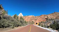 POV driving barren landscape blue sky dry climate Zion National Park Utah USA - stock footage
