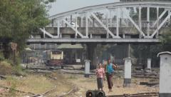 TRAIN LOCOMOTIVE: Yellow train approaches in distance, with people walking - stock footage