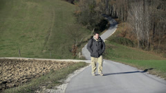 Hiker walks up the road looking at the nature around him Stock Footage