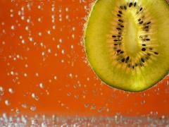 Stock Photo of kiwi in aerated water on orange background