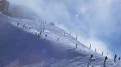 Skiers on a sunny day with lens flare Stock Footage