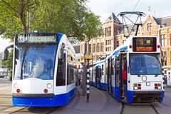 trams waiting in front of the central station in amsterdam the netherlands - stock photo