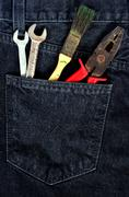 Toolkit in jeans pocket. Repairman work wear theme Stock Photos