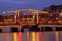 illuminated thiny bridge in amsterdam the netherlands at twiligh - stock photo