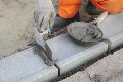 Construction site, mason using trowel Stock Photos