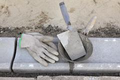 Construction site, mason equipment at curb stone - stock photo