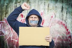 Demonstrator with a tape on a mouth and poster near to the wall Stock Photos