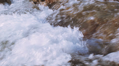 Foaming river water with red stones Stock Footage