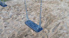 Swinging swing at a playground with low traffic and bird sounds in background Stock Footage