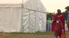 Two masai people and more scout people walking through the camp Stock Footage