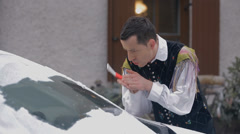 Accordion musician cleans icy window and finds that the window is damaged Stock Footage
