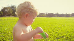 Baby boy blowing soap bubbles outdoors Stock Footage