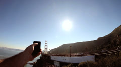 Person Smart phone technology image sun flare Golden Gate Bridge San Francisco Stock Footage