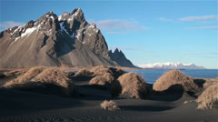 High snowy mountain peaks over black sand beach, Stokknes, Iceland Stock Footage