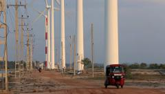 Tuk tuk motor taxi transport driving along road beneath wind farm turbines Stock Footage