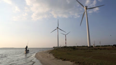 Fisherman passing wind farm turbines in boat Stock Footage
