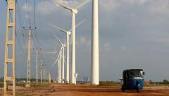 Tuk tuk motor taxi transport driving along road beneath wind farm turbines Stock Footage
