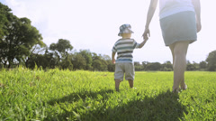 Mother and baby boy holding hands walking - stock footage