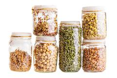 stack of different sprouting seeds growing in a glass jar - stock photo