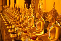 row of golden buddha statue at thailand temple. - stock photo