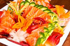 Stock Photo of mixed sashimi in white plate on wood table