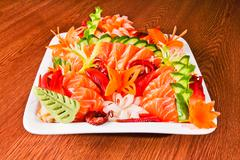 Mixed sashimi in white plate on wood table Stock Photos