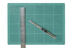 Green cutting mats with iron ruler and cuter isolated on white background Stock Photos