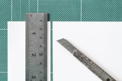 Green cutting mats with iron ruler and cuter isolated on white background - stock photo