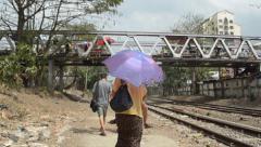TRAIN LOCOMOTIVE: People walk down tracks, one person with big umbrella - stock footage