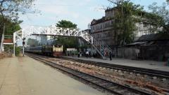 TRAIN LOCOMOTIVE: Yellow train approaches, passing under footbridge - stock footage