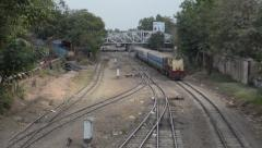 TRAIN LOCOMOTIVE: Wide shot overhead view yellow train passes beneath Stock Footage
