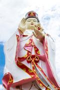 Kuan yin image of buddha with blue sky background. Stock Photos