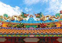 Colorful dragon statue on china temple roof with blue sky background Stock Photos