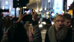 Person taking picture with smartphone of piccadilly traffic in london at nigh Stock Footage