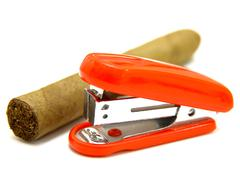 red stapler and cigar - stock photo