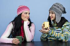 Two women discuss and enjoy a hot drink Stock Photos