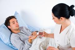 Sairaanhoitaja antaa pillereitä miespotilas Kuvituskuvat